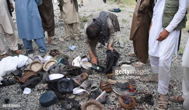 Afghan men examine the belongings of blast victims at the site of a series of explosions that targeted a funeral of a politician's son who was killed...