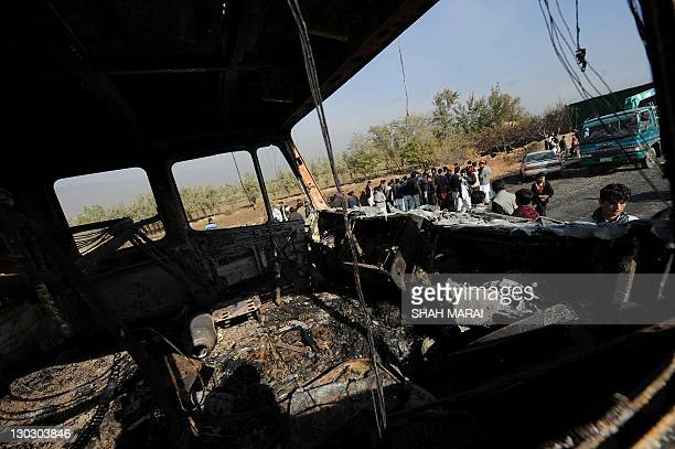 Afghan men gather at a burned out fuel truck, supplying a US-run base, after being targeted by a bomb near Bagram air base some 50, kms north of...