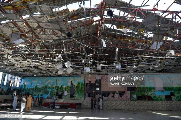 Afghan men gather in a wedding hall after a deadly bomb blast in Kabul on August 18, 2019. - More than 60 people were killed and scores wounded in an...