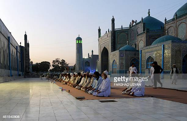 Afghan men gather to pray in the courtyard of the HazrateAli shrine or Blue Mosque in MazariSharif Across the Muslim world the faithful fast from...