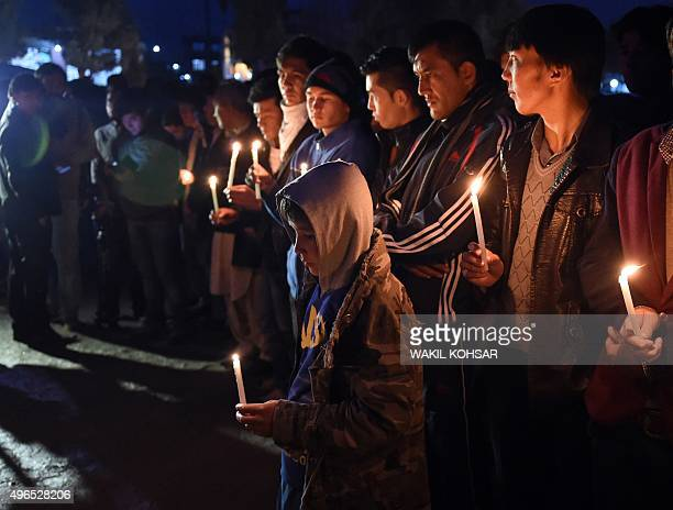 Afghan men hold a candlelight vigil during a funeral procession for a group of seven decapitated Shiite Hazaras including four men two women and one...