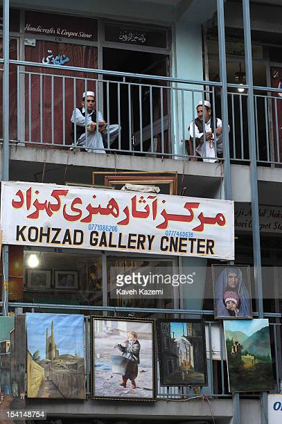 Afghan men in typical clothes sit on the balcony of a arts arcade in Chicken Street on October 17 2011 in Kabul Afghanistan Chicken Street has been a...