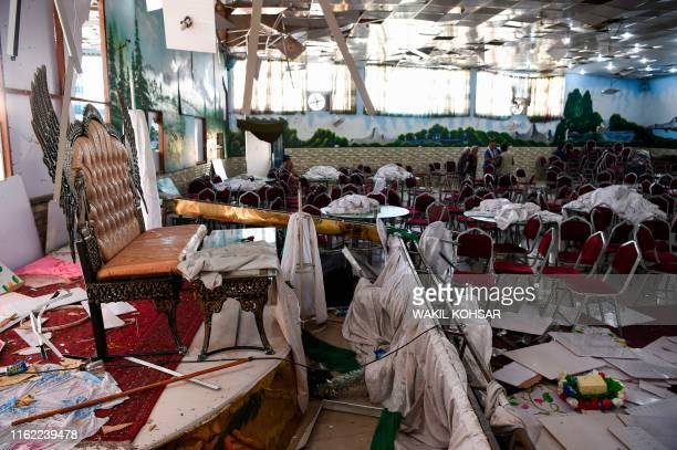 TOPSHOT Afghan men investigate in a wedding hall after a deadly bomb blast in Kabul on August 18 2019 More than 60 people were killed and scores...