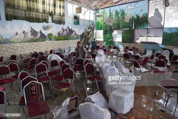 Afghan men investigate in a wedding hall after a deadly bomb blast in Kabul on August 18 2019 More than 60 people were killed and scores wounded in...