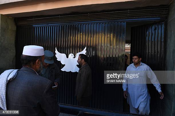 Afghan men leave the Park Palace guesthouse in Kabul on May 14 2015 An American was among five people killed when gunmen stormed a downtown Kabul...