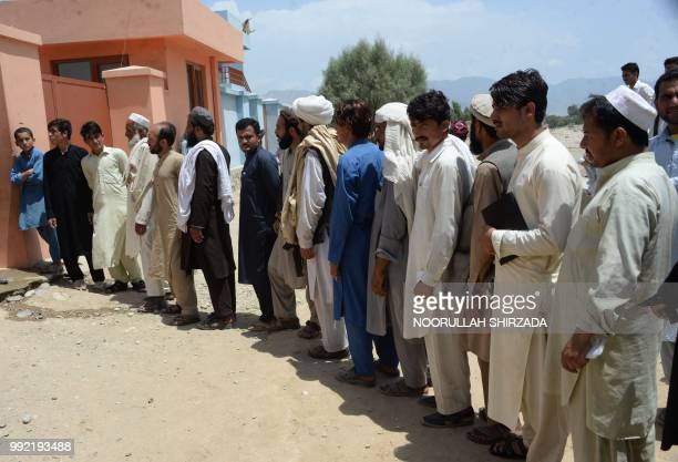 Afghan men line up to register themselves to vote in upcoming parliamentary and district council elections in Bihsood District on the outskirts of...