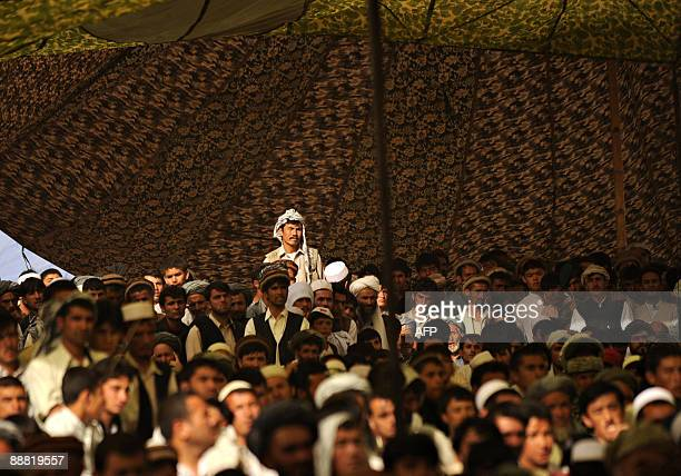 Afghan men listen to unseen Afghanistan's former foreign affairs minister and presidential election candidate Abdullah Abdullah as he campaigns at...