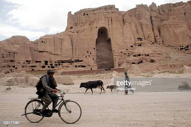 Afghan men pass the ruins of the ancient budha statues that once stood on July 30 2010 in the central Afghan province of Bamiyan Bamiyan some 200...