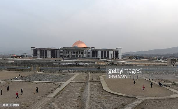 Afghan men play football as construction takes place of a new Parliament building in Kabul on February 10 2015 AFP PHOTO/ SHAH Marai