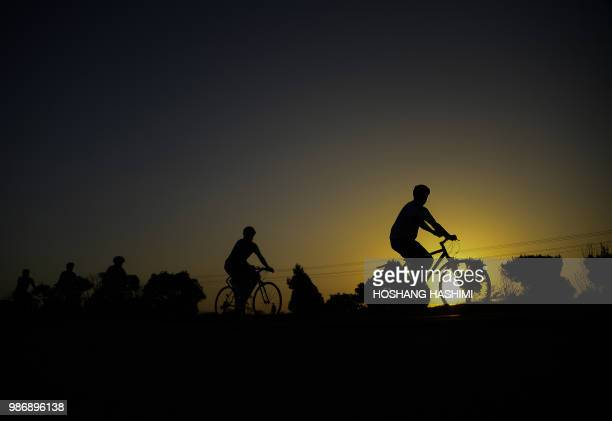 TOPSHOT Afghan men ride their bicycles during a daily practice on the outskirts of Herat on June 29 2018