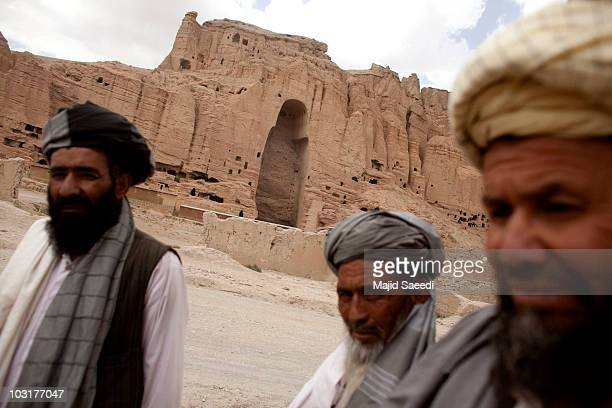 Afghan men stand near the ruins of the ancient budha statues that once stood on July 30 2010 in the central Afghan province of Bamiyan Bamiyan some...