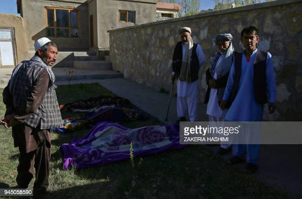 Afghan men stand over dead bodies at the site of an attack by Taliban militants on a government compound in the Khwaja Omari district in the...