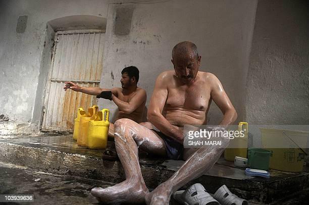 Afghan men take a bath at a traditional hamam bathhouse in Kabul on September 9 2010 ahead of the Eid AlFitr festival The threeday festival which...