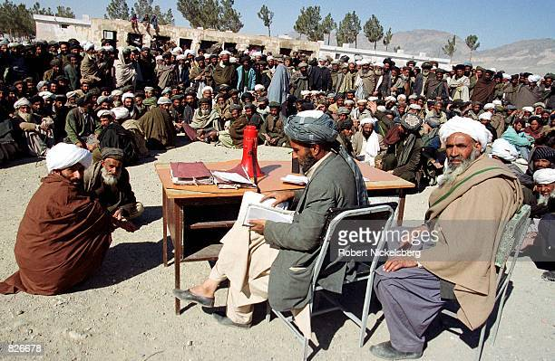 Afghan men wait for their names to be called for the distribution of aid rations February 23 2001 at a refugee camp in Herat Afghanistan Refugees...