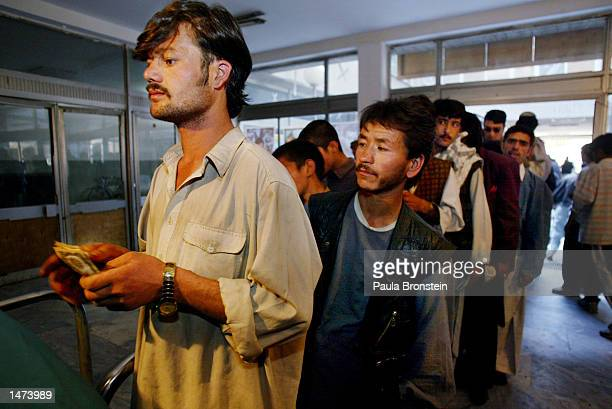 Afghan men wait in line to buy tickets for a movie at he Park Cinema October142002 in Kabul Afghanistan Tickets cost around 10 cents Only men are...