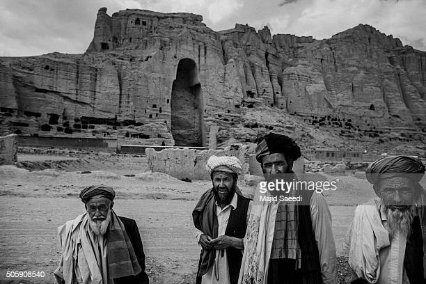 Afghan men waiting for the bus in front of remains of Buddha statue in Bamiyan