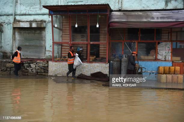 Afghan men walk along a roadside after heavy rains in Kabul on April 16 2019 Torrential rainstorms have lashed droughtstricken Afghanistan in recent...