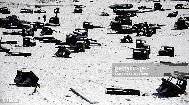 Afghan men walk amongst the remains of Russian military vehicles on the outskirts of Kabul on February 14 2009 on the eve of the 20th anniversary of...