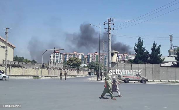 Afghan men walk on a road as smoke rises from the site of an attack in Kabul on July 1 2019 Dozens of people were wounded with fatalities feared as a...