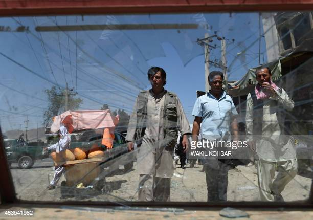 Afghan men walk past the damaged window of a roadside stall near the site of a bomb attack near the entrance to Kabul's international airport in...