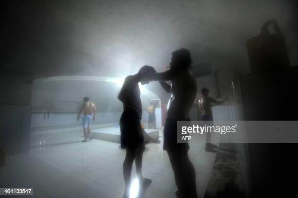 Afghan men wash at a traditional 'hamam' bathhouse in MazariSharif on January 20 2014 Afghans usually come in the morning for onehour sessions inside...