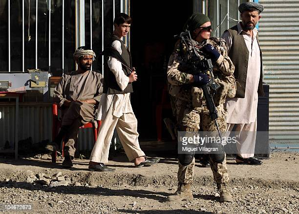 Afghan men watch a German female Bundeswehr soldier during a patrol on October 2 2010 in Feyzabad Afghanistan Germany has more than 4500 military...