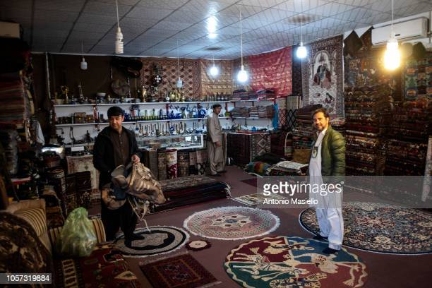 Afghan men work in a market shop inside the Camp Arena military base near Herat airport on November 04 2018 in Herat Afghanistan The Italian...