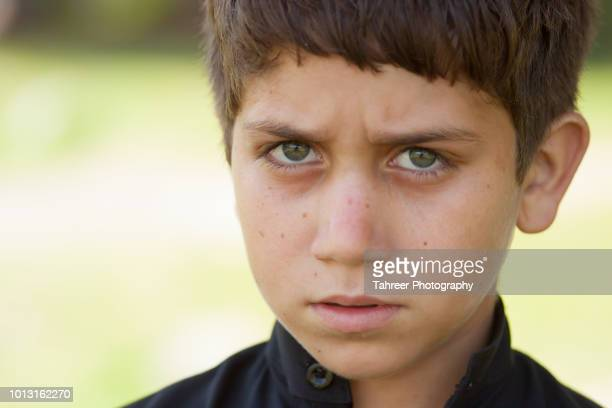 afghan migrant child with colored eyes - cute pakistani boys stock photos and pictures