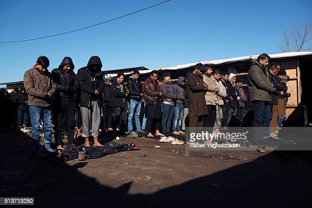 Afghan migrants pray in front of a makeshift shop during the traditional Muslim Friday prayers inside the 'Jungle' camp as agents dismantle shelters...