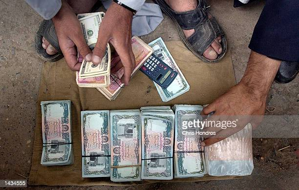 Afghan money traders count out piles of American dollars Pakistani rupees and Afghan Afghanis September 27 2002 in Kabul The Afghani the official...