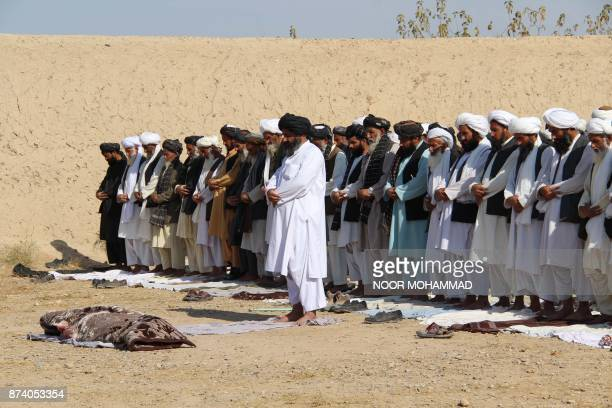 Afghan mourners and relatives pray in front of the slain Afghan Local Police officer killed during a wave of Taliban attacks in Helmand on November...