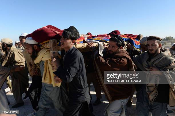 Afghan mourners carry the coffin of one of the 13 victims of a suspected US airstrike in the Achin district of Nangarhar province on January 12 2018...
