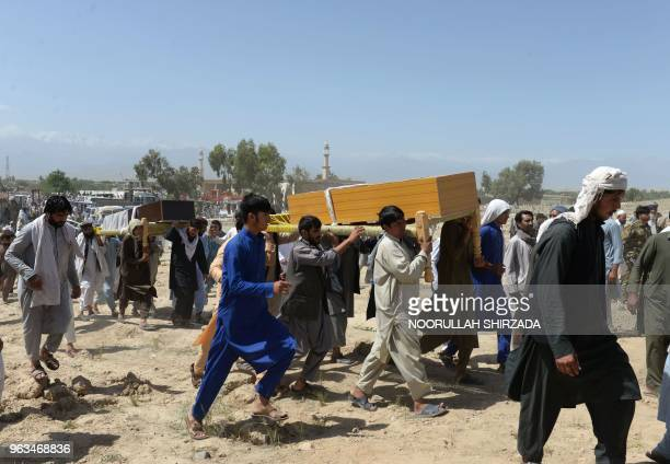 Afghan mourners carry the coffin of one of the nine people killed during an overnight raid by Afghan forces in Chaparhar district on the outskirts of...