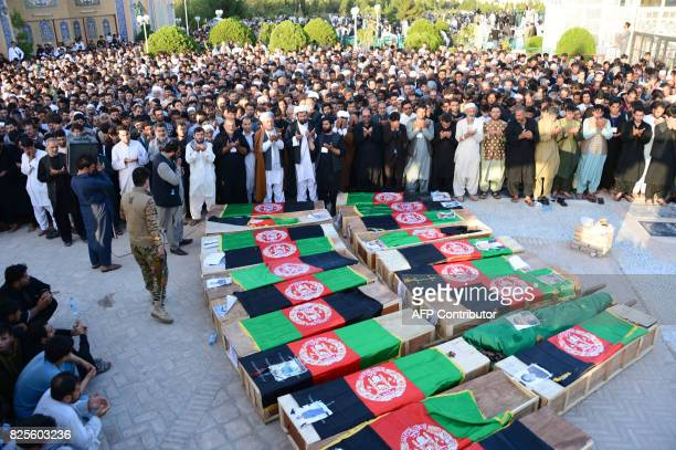 Afghan mourners offer funeral prayers near the coffins of victims following a mosque attack that killed 33 people in Herat on August 2 2017 Thousands...