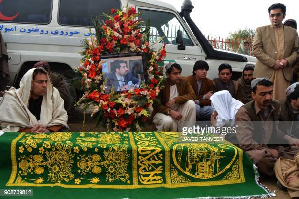 Afghan mourners sit around the coffin of Mufti Ahmad Farzan a member of the High Peace Council who died during an attack by armed insurgents at...