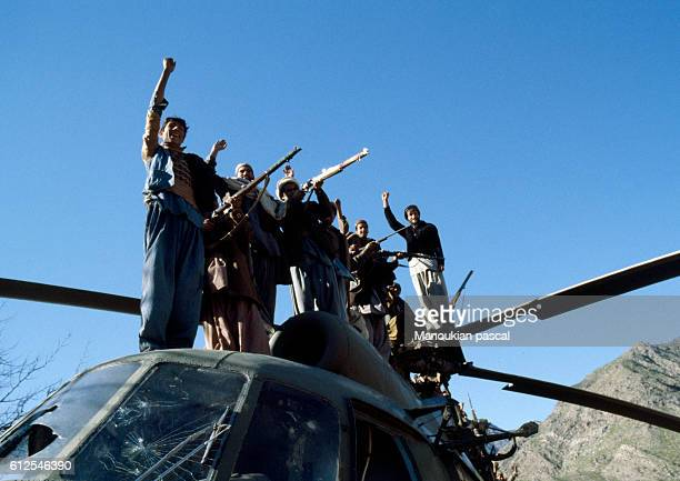 Afghan Mujahideen standing on a destroyed Russian helicopter. They fought against the Soviet invasion of Afghanistan during the 1980s following the...