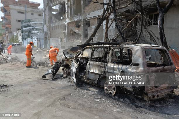 Afghan municipality workers work to clear up the site of an attack in Kabul on July 29 a day after the deadly assault targeting a political campaign...