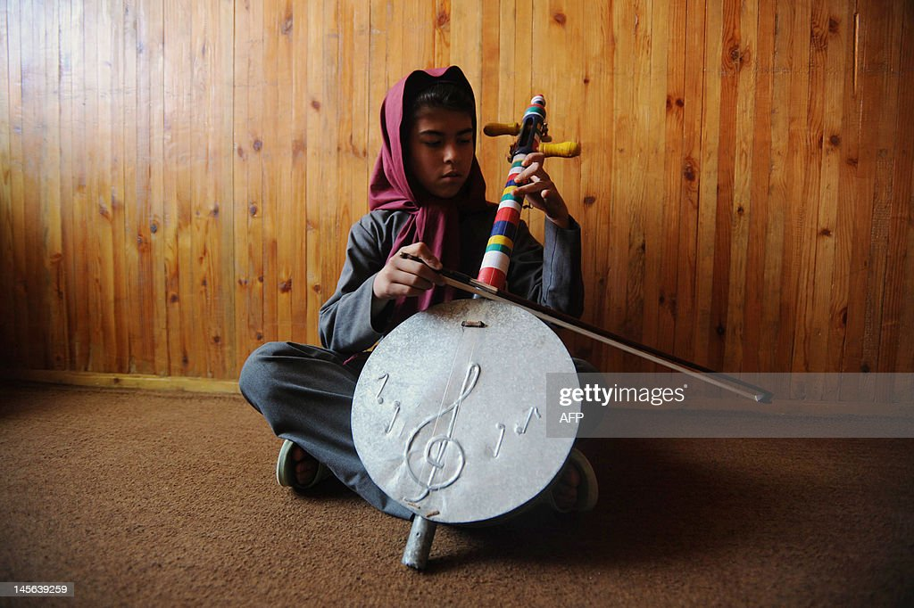 Afghan music student Mushgan plays a traditional musical