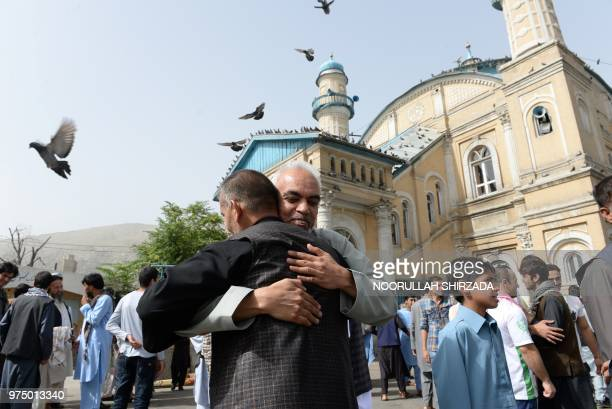 Afghan Muslims hug each other after offering prayers at the start of the Eid alFitr holiday which marks the end of Ramadan at the Shahe Do Shamshira...
