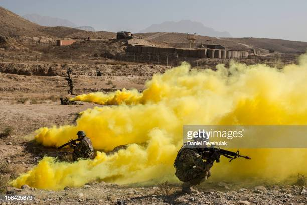 Afghan National Army cadets secure the perimeter as smoke bombs simulating detonated IED's cover the area during a Taliban capture military exercise...