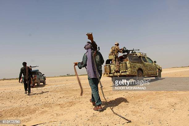 Afghan National Army commandos and Afghan militia forces take position during a military operation in Helmand province on October 4, 2016. / AFP /...