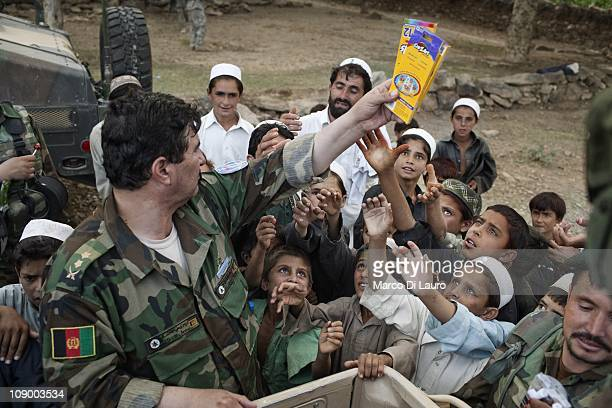 Afghan National Army LTC Farowq 2nd Kandak 1st Brigade 203 Corps Commander distributes humanitarian assistance to local children as US Army Embedded...