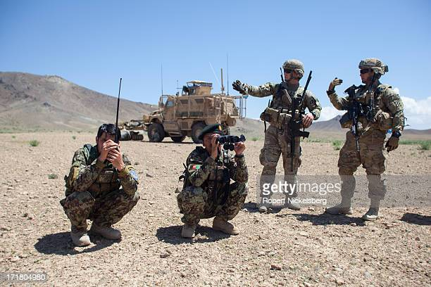 Afghan National Army officers, left, view the landscape during a joint operation with U.S. Army soldiers from the 4th Brigade, 3rd Infantry Division,...