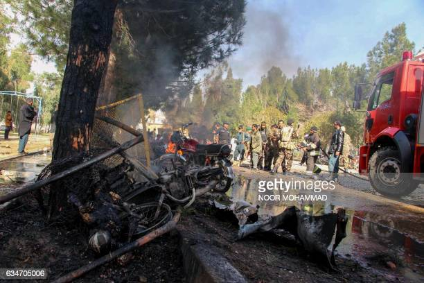 Afghan National Army soldiers and firefighters extinguishe fire at the site of a suicide car bomb attack in Lashkar Gah in Helmand Province on...