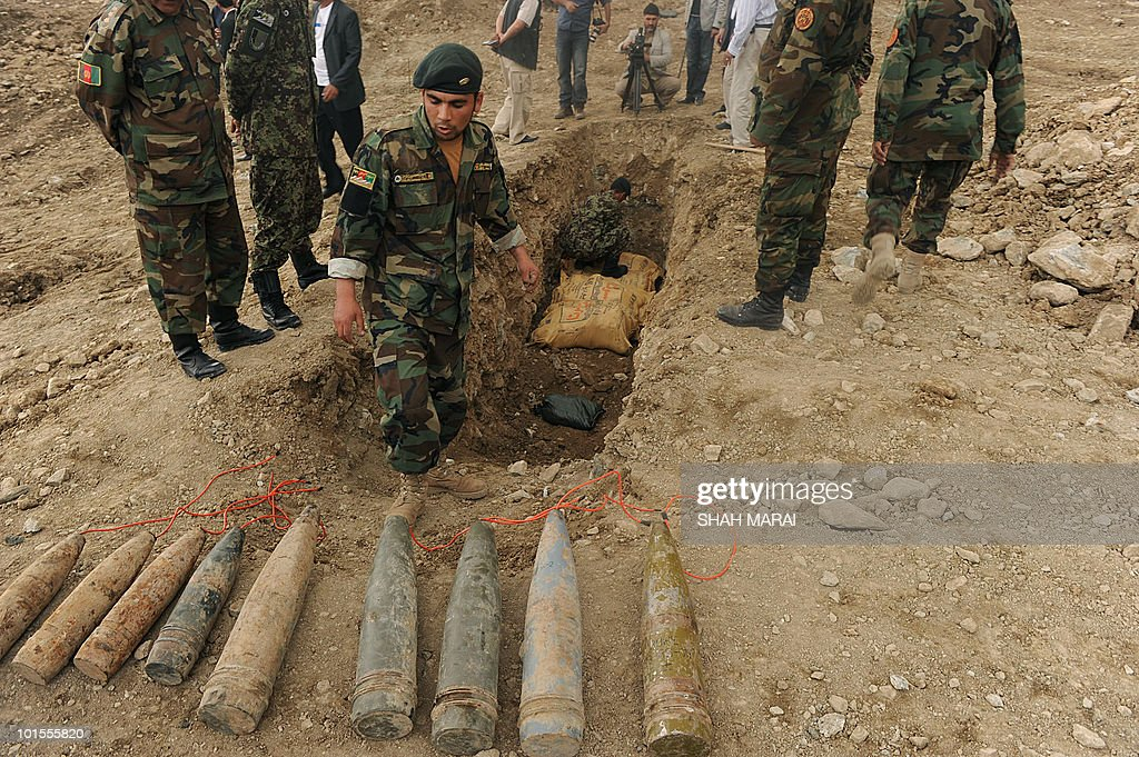 Afghan National Army (ANA) soldiers look at shells to be used as explosives to destroy a cache of ammonium nitrate fertilizer in a controlled explosion on a hillside north of Kabul on April 21, 2010. The fertiliser is a major ingredient in improvised explosive devices, or IEDs, which are used by the Taliban insurgents against foreign and Afghan forces, as well as civilians, to devastating effect. Military officials have said that 90 percent of foreign troops deaths are caused by IEDs. AFP PHOTO/SHAH Marai