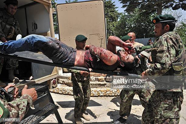 Afghan National Army soldiers remove the body of a dead civilian from the Spozhmai Hotel in Qargha lake in the outskirts of Kabul on June 22...
