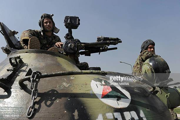 Afghan National Army soldiers sit on the top of a Russianmade T62 tank during a weapons exhibition of military equipment donated to the ANA by the...