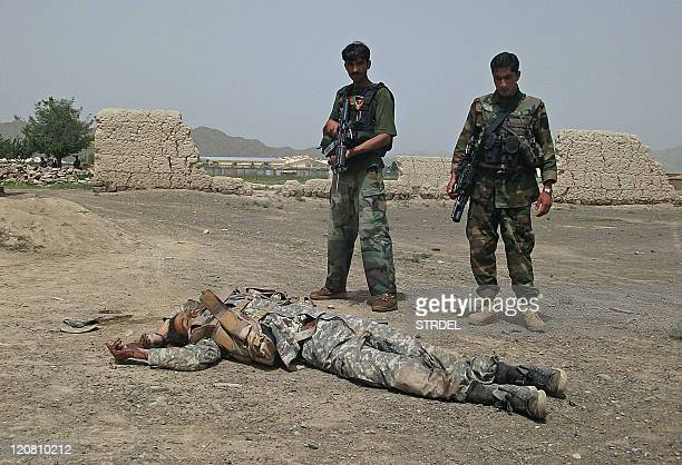 Afghan National Army soldiers stand guard near the body of a suicide attacker near US military camp Salerno on the outskirts of Khost city on August...