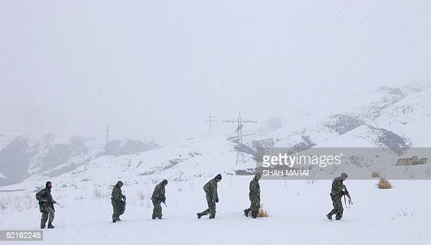 Afghan National Army soldiers walk in deep snow as they make they way to the crash site of a civilian airliner in Mullah Omer District some 30kms...