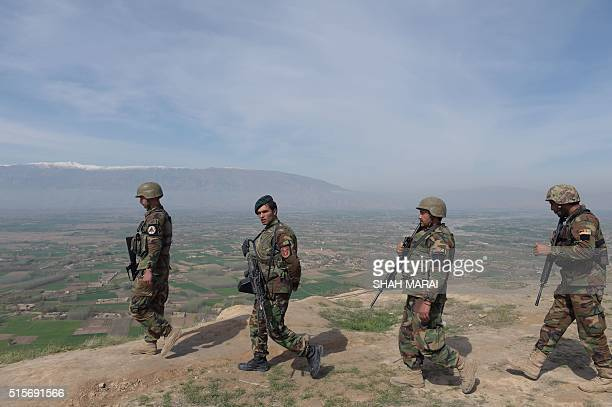 Afghan National Army soldiers walk through DandeGhori district in Baghlan province on March 15 following weeks of heavy battles to recapture the area...